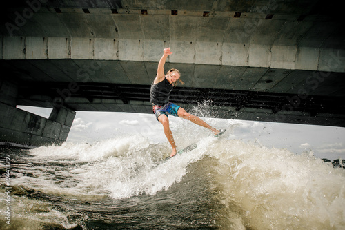 Poster Nautique motorise Active athletic guy wakesurfing on the board down the river against the concrete bridge