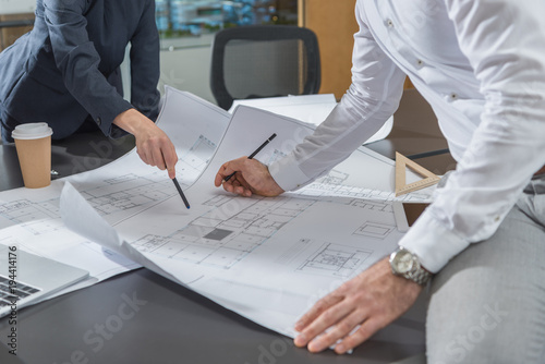 Fotografia  cropped shot of stylish architects working with building plans together at offic