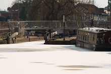 Frozen Lake With Canal Lock Boat And Bridge In Winter