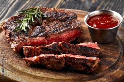 Papiers peints Steakhouse Juicy steak medium rare beef with spices on wooden board on table