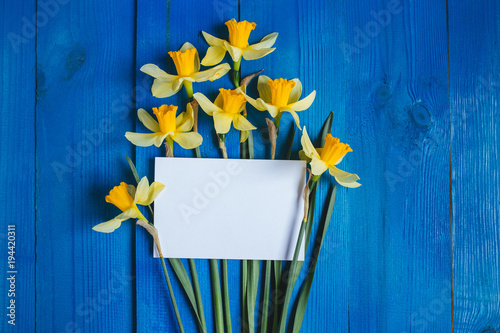 Flowers Greeting Card . Spring background with daffodils bouquet on wooden table