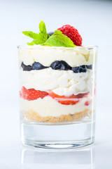 Panel Szklany Do cukierni Sweet tiramisu dessert with berries and ice-cream in a glass isolated on white background