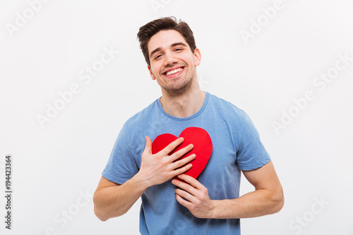 Pleased man in t-shirt hugging paper heart