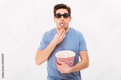 Poster  Shocked man in t-shirt and 3d glasses eating popcorn