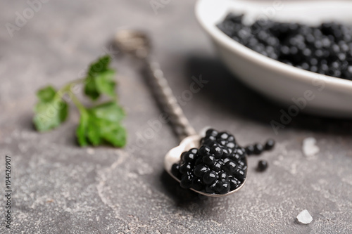 Spoon with delicious black caviar on grey background