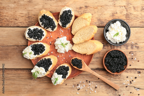 Sandwiches with delicious black caviar and cottage cheese on wooden plate