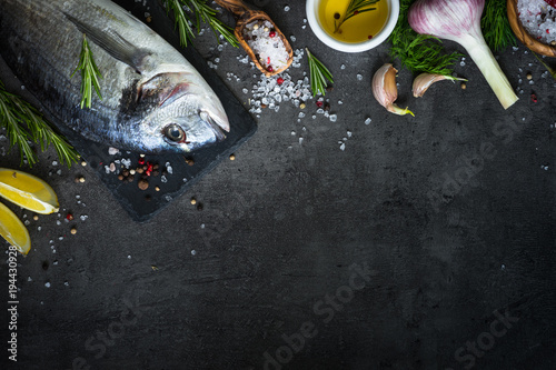 Dorado and ingredients for cooking at black.