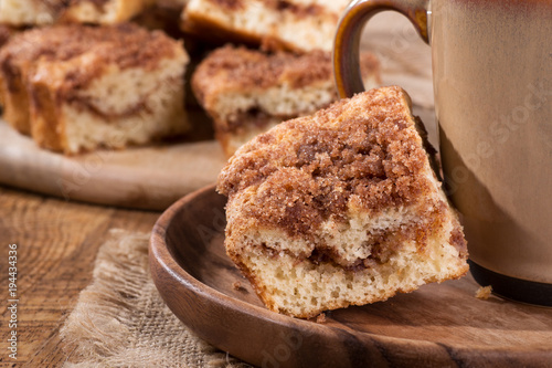 Tuinposter Koekjes Closeup of a piece of cinnamon swirl crumb cake and coffee cup on a wooden plate