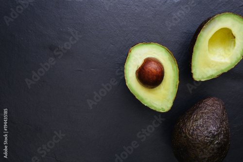 Fotografia, Obraz Avocado half on dark background