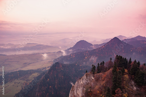 Fantastic mountain landscape, surreal pink and purple sky, the mountains are covered with trees