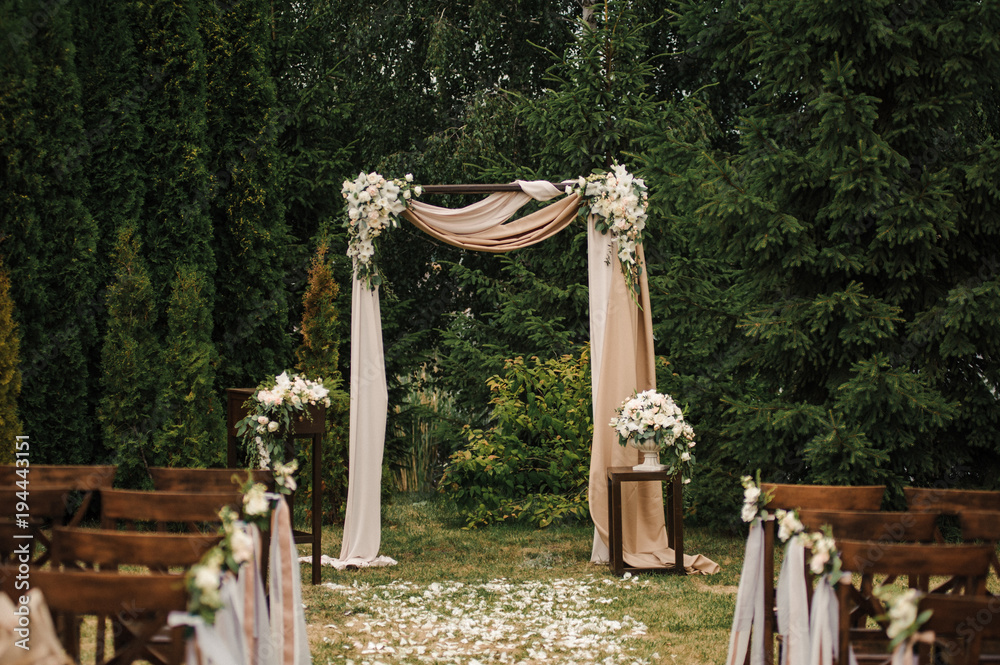Fototapety, obrazy: Very beautiful outside ceremony. classical wedding in forest. The arch is wooden. White flowers. Brown chairs. Rite. Bride and groom. Decor. Floristics. In the open air. Path from the petals of roses.