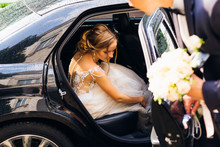The Beautiful Bride Sits In A Black Car And The Groom Wants To Close The Door After