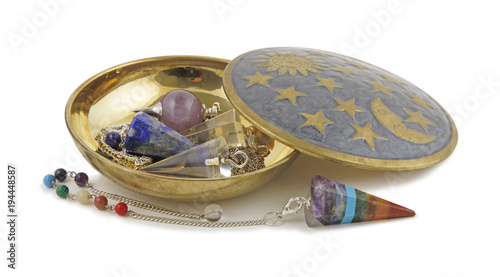 Selection of Radionics Dowsing Pendants - Brass dish on a white background containing three different dowsing pendulums and one Chakra coloured pendant laid in front