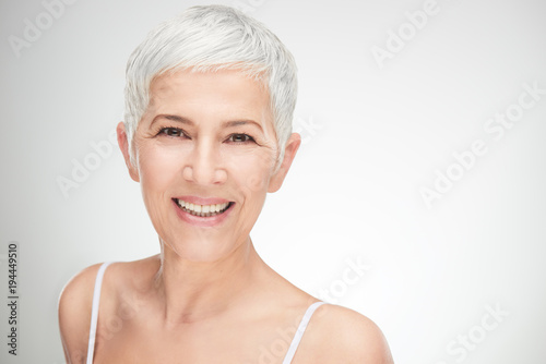 Portrait of beautiful senior woman in front of white background. Poster
