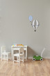 grey wall baby room small table and chair concept with toys. Parachute patterns on the wall.