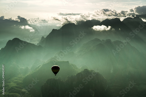 Valokuva  Taking a breathtaking hot air balloon ride over the city of Vang Viegn overlooking the stunning countryside of Laos during sun set