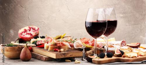 Fototapeta Italian antipasti wine snacks set. Cheese variety, Mediterranean olives, pickles, Prosciutto di Parma and salami obraz
