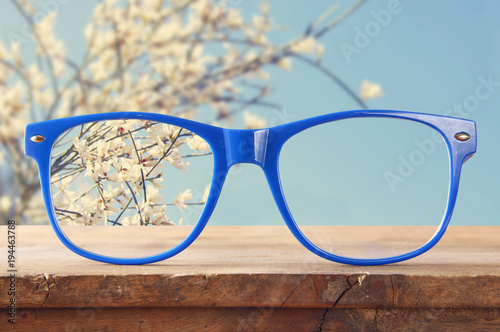 Fotografía  hipster glasses on a wooden rustic table in front of white flowers