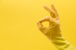 canvas print picture - Okay hand gesture made by a hand in a yellow rubber cleaning glove