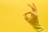 Okay hand gesture made by a hand in a yellow rubber cleaning glove