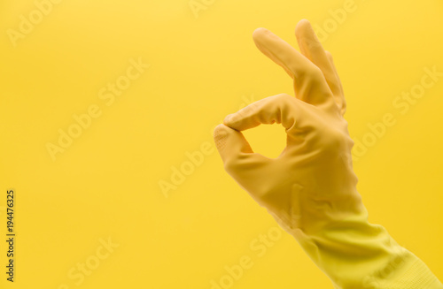 Fotografija  Okay hand gesture made by a hand in a yellow rubber cleaning glove