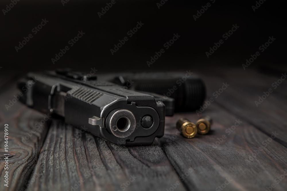 Fototapeta black pistol and cartridges on a wooden background