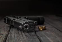 Black Pistol And Cartridges On...