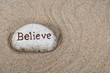 close up of stone with believe text in raked beach sand pattern