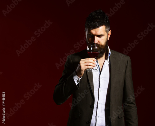Sommelier with beard on burgundy background. Degustation and winetasting concept