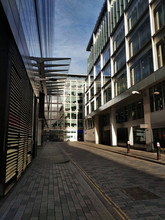 Double-decker Bus Passing On City Street Along Modern Shopping And Business Office Buildings In London
