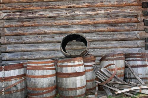 Fotografie, Obraz  Alte Fässer vor einer Blockhütte