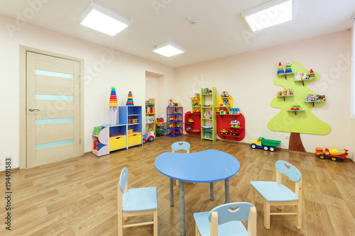 Blue table for classes with children and light pink colored game room with in the kindergarten