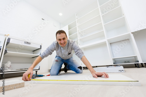Photo Young man dressed casual assembling furniture in new house