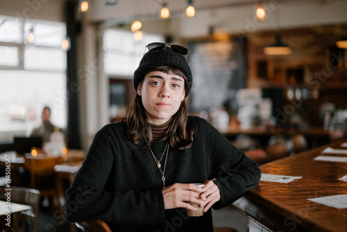 Young woman wearing black hat and sun glasses posing in the vintage interior drinking coffee