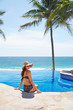 Beautiful woman relaxing at luxury resort by infinity pool