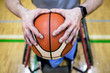 Close-up shot of disabled athlete hands holding a basketball