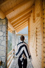 Young Woman Covered With Blanket Standing In Front Of The Wooden Cabin