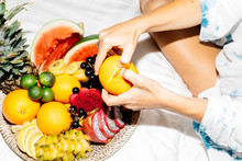 Woman Laying On White Bed Peeling And Eating Brightly Colored Orange From Large Tray Of Fruit