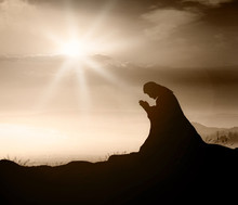 Miracle Salvation Concept: Silhouette Jesus Christ Of Nazareth Kneeling And Praying At Garden Of Gethsemane Background