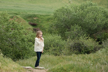 Young Girl Standing On Hillsid...