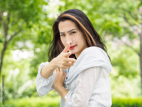 Beautiful young brunette Asian woman aiming at camera with hand gun