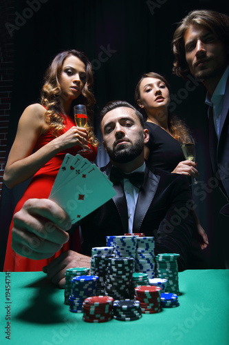 Платно concentrated men and women playing poker in casino