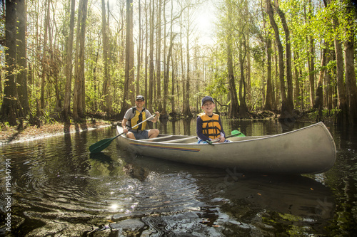 Adventuresome Father and son canoeing together on a beautiful river in a thick forest