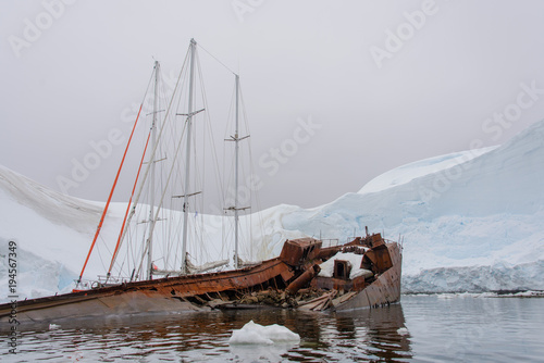 Foto auf Gartenposter Antarktis Two sailing yachts in the antarctic sea moored to rusty wreck