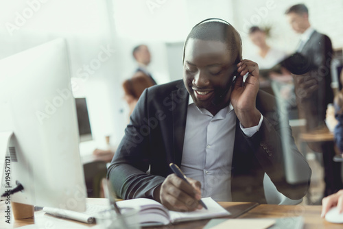 A black guy works as a call center operator.
