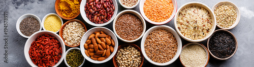 Poster Graine, aromate Superfoods and cereals selection in bowls: quinoa, chia, goji berry, mung bean, buckwheat, bean, turmeric, polba, bulgur, lentil, sesame, flax seed, wild rice, almond on grey concrete background