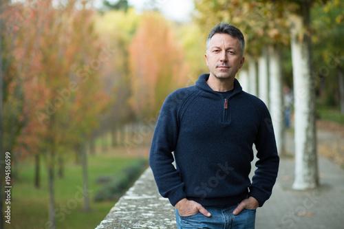 Handsome middle-aged man walking autumn park Tableau sur Toile