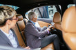 Senior businesswoman and her assistant sitting in limousine talking and working