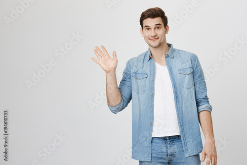 Portrait of athletic handsome man waving and looking friendly at