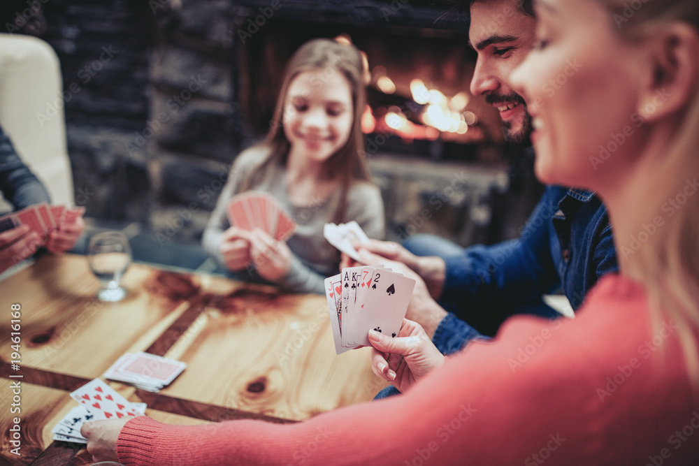 Fototapeta Young family playing card game